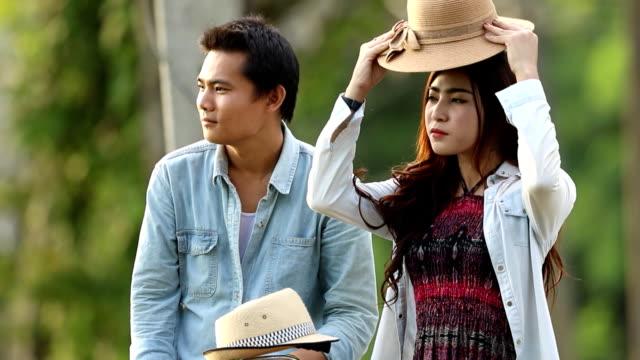 Schönes Mädchen helfen ihrem Freund einen Hut tragen