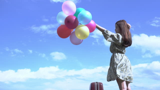 beautiful girl holds a balloon in the outdoors with the mountains and rivers in the background. conceive the bright cheerfulness of asian girls. - children only stock videos & royalty-free footage