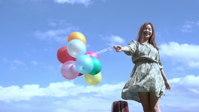 beautiful girl holds a balloon in the outdoors with the Mountains and rivers in the background. Conceive The bright cheerfulness of Asian girls.