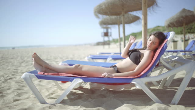 beautiful girl in a deck chair in the beach - legs crossed at ankle stock videos and b-roll footage