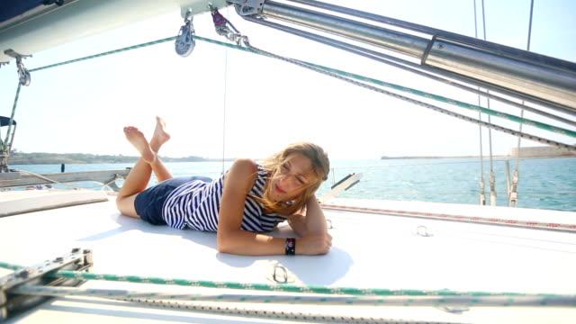 vidéos et rushes de belle jeune fille à un t-shirt rayé reposant sur un yacht - équipe de voile