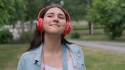 beautiful girl in red headphones jumps and listens to music