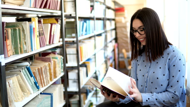 beautiful girl in the library / bookstore. bookshelf with old books - librarian stock videos & royalty-free footage