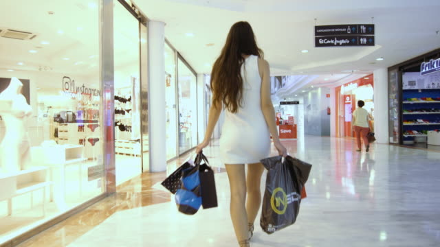 a beautiful girl in the mall with shopping bags - einkaufstasche stock-videos und b-roll-filmmaterial