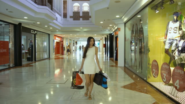 a beautiful girl in the mall with shopping bags - clothes shop stock videos and b-roll footage
