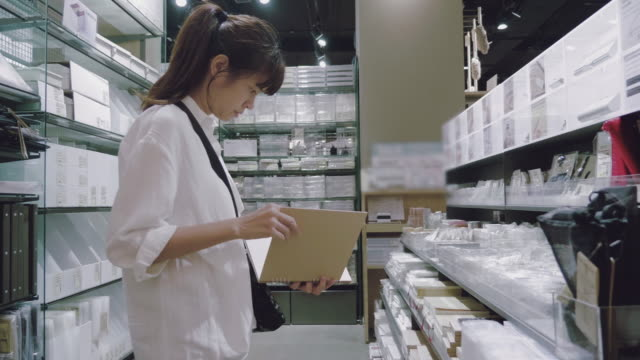 beautiful girl is choosing a book in the supermarket. - bookseller stock videos and b-roll footage