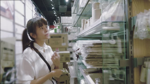 beautiful girl is choosing a book in the supermarket. - postcard stock videos and b-roll footage