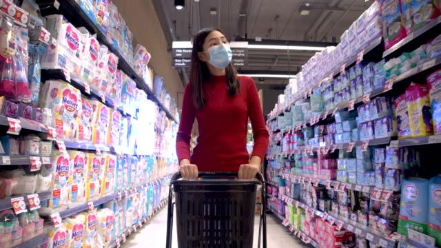 vídeos de stock, filmes e b-roll de garota bonita está fazendo compras no shopping e ela usa uma máscara facial protetora. - fralda
