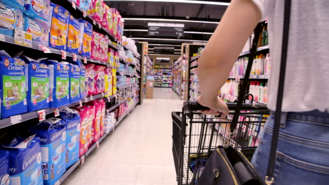 beautiful girl is shopping at the market mall. - shopping trolley stock videos & royalty-free footage