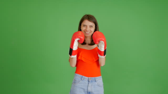 beautiful girl jokingly boxing on a green background