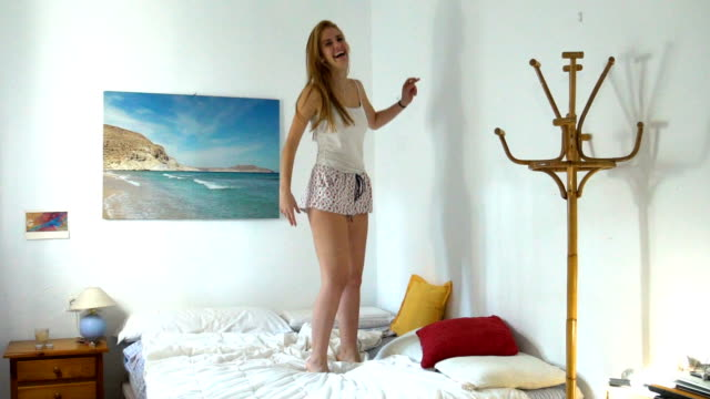 vidéos et rushes de a beautiful girl jumping in her bed in a bright bedroom in pijama - 18 19 ans