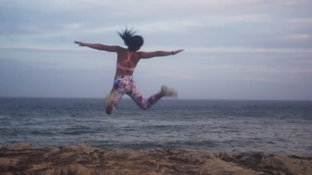 Beautiful girl jumps into air near the ocean (slow motion)