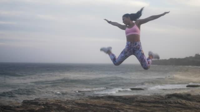 Mooi meisje springt in de lucht in de buurt van de Oceaan