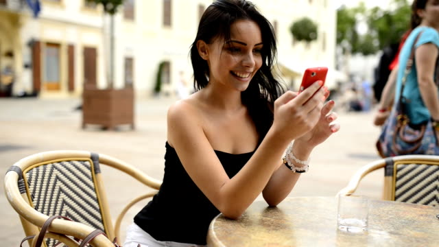 Beautiful girl playing with mobile phone at the table.