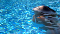 Beautiful girl pops up under water at the pool. Young woman emerges from under the aqua at the basin of hotel. Brunette relaxing on sunny day. Summer vacation or holiday concept. Close up Slow motion