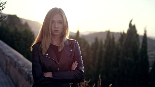 beautiful girl posing in the sunlight. sadness - leather jacket stock videos and b-roll footage