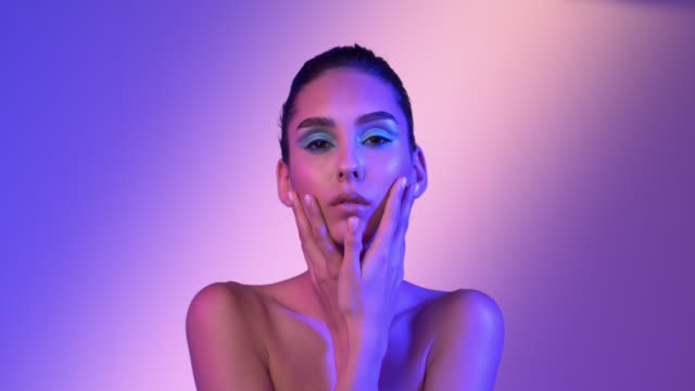美しい女の子は滑らかに光沢のある肌と顔の近くに彼女の手を移動します。多色の照明。 - アイシャドウ点の映像素材/bロール