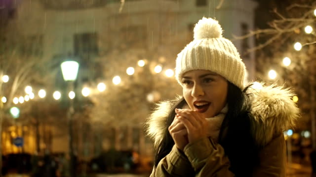 beautiful girl standing in the cold on the street with christmas lights - slow motion - slovakia stock videos & royalty-free footage