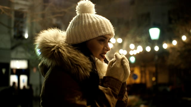 beautiful girl standing in the cold on the street with christmas lights - slow motion - cap stock videos & royalty-free footage