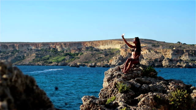 beautiful girl sunning on a high cliff by the sea and taking selfie - little girls flashing stock videos and b-roll footage
