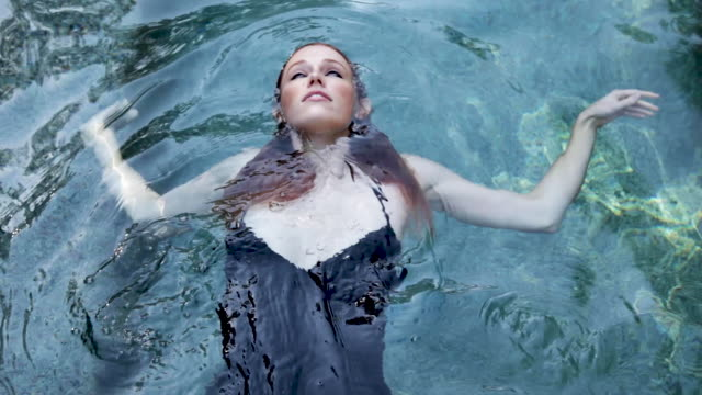 beautiful girl swimming in pool wearing dress - black dress stock videos & royalty-free footage