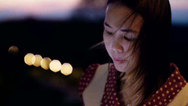 Schöne Mädchen nutzt eine Smartphone in der Abenddämmerung