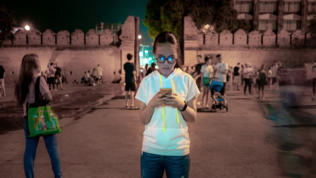 schönes mädchen mit einem smartphone am thapae-tor chiang mai - multitasking stock-videos und b-roll-filmmaterial