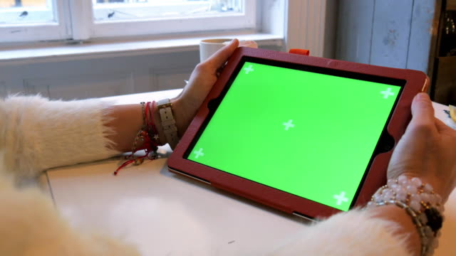 Schöne Mädchen mit Green-Screen-Tablet in Coffee-Shop