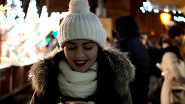 クリスマス市場 - スロー モーションを介して携帯電話と歩いている美しい少女 - glove点の映像素材/bロール