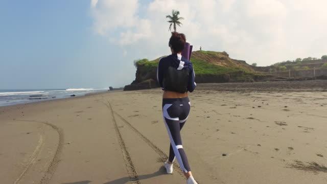 Schöne Mädchen geht mit Yoga-Matte am Strand von Bali