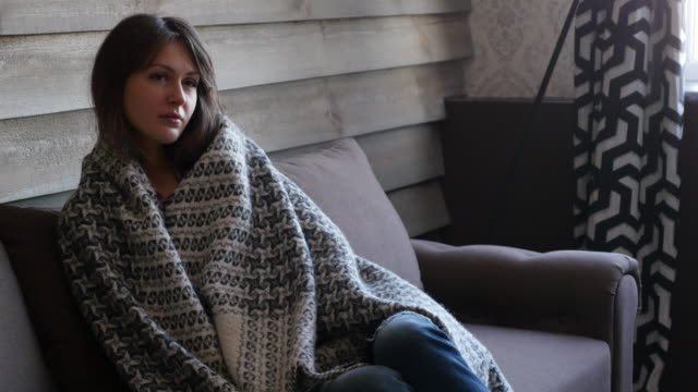 beautiful girl with a blanket sitting on a sofa - blanket stock videos and b-roll footage