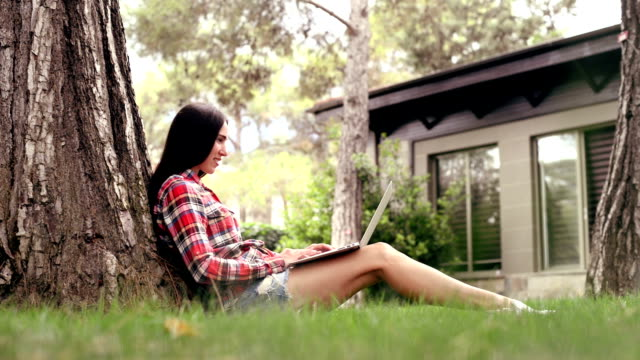 beautiful girl with a laptop sitting on the grass - shorts stock videos & royalty-free footage