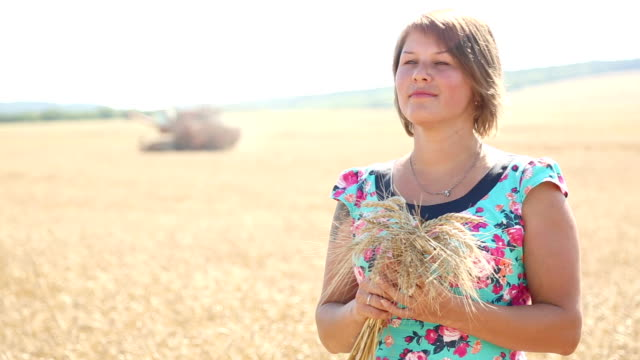 beautiful girl with ears of wheat in field