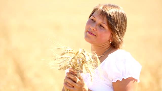 stockvideo's en b-roll-footage met beautiful girl with ears of wheat in the field - volkorentarwe