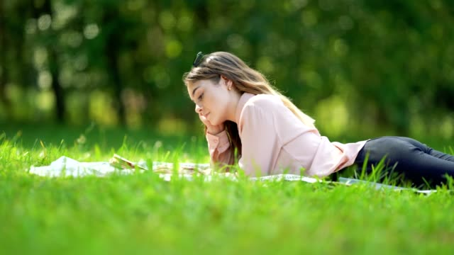 a beautiful girl with long hair reads a book lying on the grass in the park on a sunny day - brown hair stock videos & royalty-free footage
