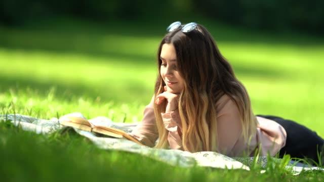 vídeos y material grabado en eventos de stock de una hermosa chica con el pelo largo lee un libro tumbado sobre la hierba en el parque en un día soleado - robin day