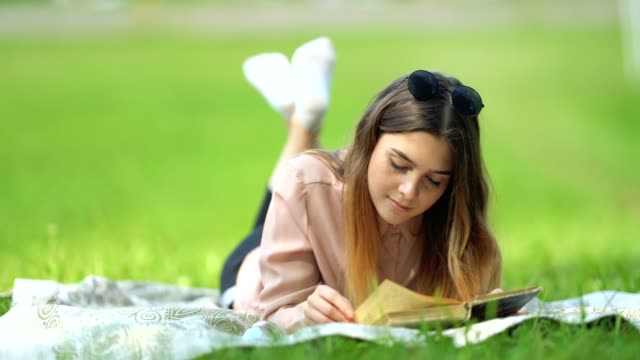 a beautiful girl with long hair reads a book lying on the grass in the park on a sunny day - robin day stock videos & royalty-free footage