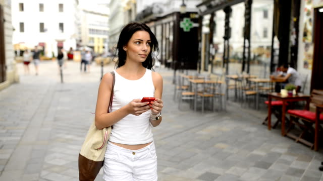 Beautiful girl with mobile phone as navigation on the street.