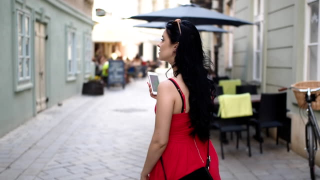 beautiful girl with mobile phone on the street - slow motion - vista posteriore video stock e b–roll