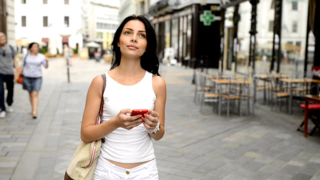 Beautiful girl with mobile phone on the street.