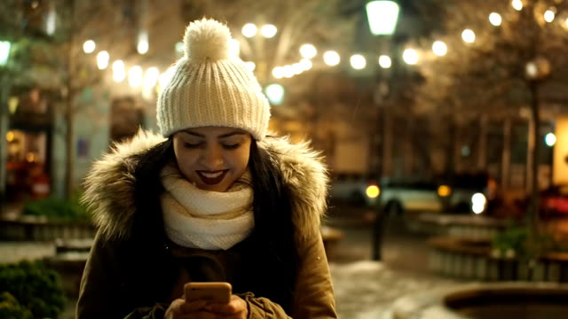 beautiful girl with mobile phone on the winter street with christmas lights - slow motion - slovakia stock videos & royalty-free footage