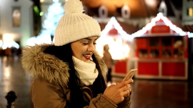 beautiful girl with mobile phone on the winter street with christmas lights - slow motion - 1 minute or greater stock videos & royalty-free footage