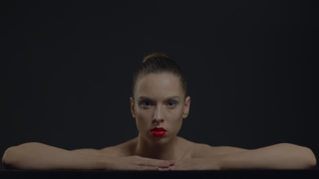 vidéos et rushes de une belle fille avec des lèvres rouges tourne lentement sa tête. maquillage. - cou humain