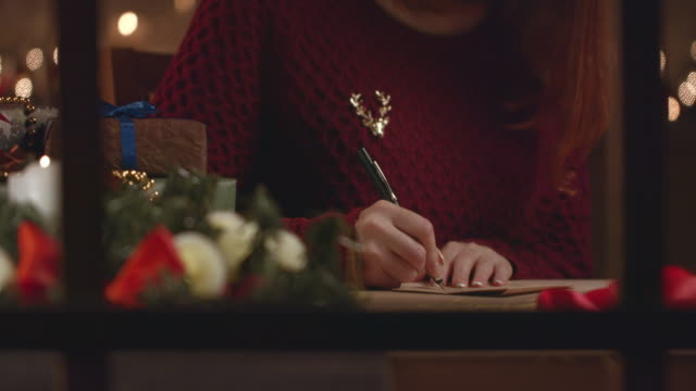a beautiful girl writes a christmas letter to her friends. - christmas card stock videos & royalty-free footage