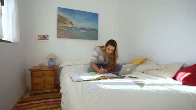 A Beautiful Girls Studying In A Bright Bedroom With Notes ...