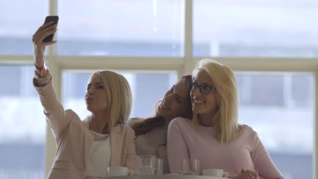 vídeos y material grabado en eventos de stock de hermosas chicas tomando selfie en restaurante. - mesa baja de salón