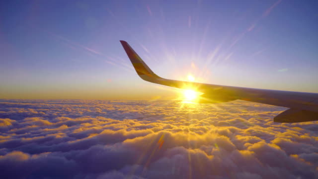 beautiful golden sunset sunrise flight with sun light beam and airplane wing - passenger point of view stock videos & royalty-free footage