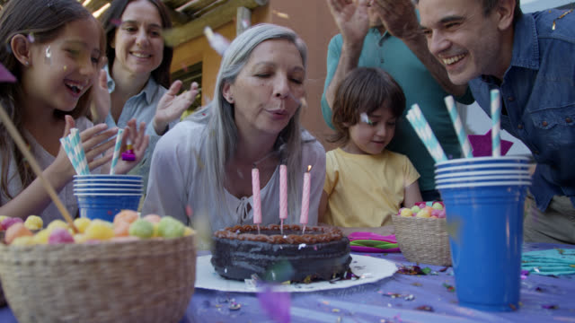 beautiful grandmother blowing out her birthday candles making a wish as her family celebrates next to her all smiling - birthday cake stock videos & royalty-free footage