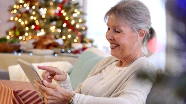 Schöne Großmutter durchläuft die Weihnachtsbilder auf digital-Tablette