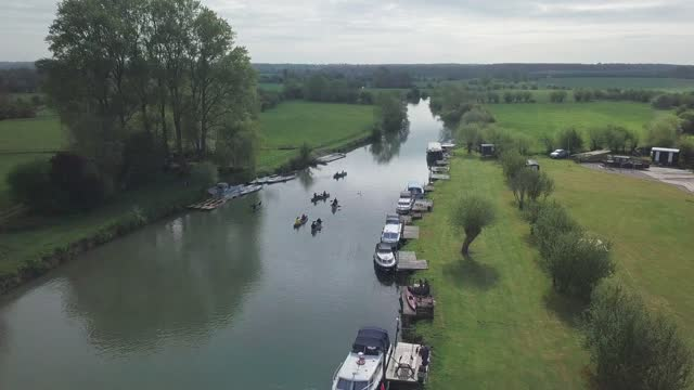 beautiful green landscape and tourists kayaking along thames river in southern england - aerial shot - barge stock videos & royalty-free footage